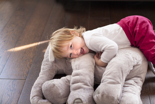 child snuggling with stuffed animal on wood floor